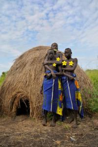 Mursi young ladies with their hut